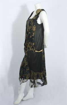 he under layer is a slip of black satin; the outer layer is fashioned from black knotted net lace embroidered with black silk floss leaves and a zigzag pattern of burnished gold floss. The large gold lamé rose at the shoulder and the black-and-gold Deco clasp at the hipline are fabulous period details.The dress slips over the head with no closures. The petal-shaped hemline is to die for!