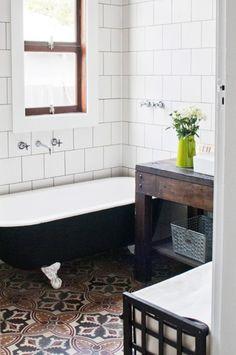 Bathroom with subway tile, black grout, clawfoot tub, patterned encaustic tile floor, via @sarahsarna.