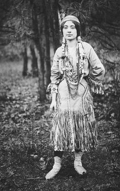 An old photograph of an Native American Maiden in Traditional Dress.