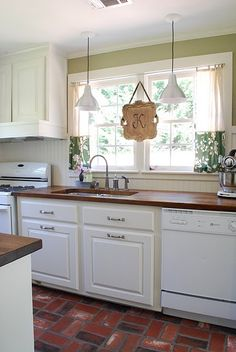 love the wall color, the beadboard backsplash, the dark countertops with the white cabinets