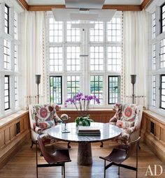 The custom-made Georgian-style wing chairs in the library alcove are upholstered in a hand-embroidered fabric from Robert Kime; the pendant lamp is by Maurer, and the TG-10 sling chairs and marble Angelo Mangiarotti table are vintage. Robert Couturier