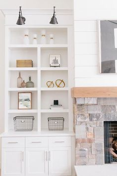 Chic cottage living room features a stone fireplace accented with a wood mantle under art next to built in shelves and cabinets illuminated by Schoolhouse Electric Princeton Sconces.