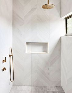 Minimalist Home Interior modern bathroom with modern white herringbone tile in walk in tile shower, white tile shower wiht gold shower head, minimalist bathrooom decor