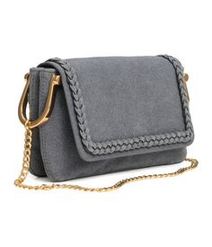 Small imitation leather shoulder bag with a regenerated-leather finish. Metal chain shoulder strap, flap with decorative braided trim and magnetic closure, and two compartments. Lined. Size 1 1/2 x 5 x 8 1/4 in.