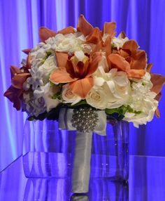 Elegant bride bouquet with touches of red phalaenopsis orchids. #wedding #flowers #orchids #roses