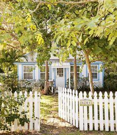 Nothing adds charm to a front yard like a white picket fence, as evidenced by this cute-as-a-button Florida cottage.