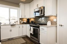 The Kingston kitchen cabinets featuring white painted cabinets, granite countertops, Oil rubbed bronze hardware, and full back splash.