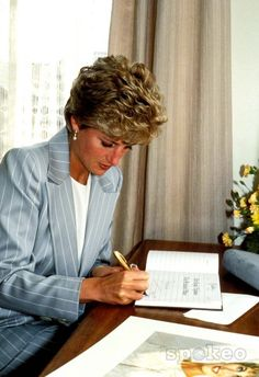 Diana, Princess of Wales writes in her day planner at her desk in Kensington Palace.