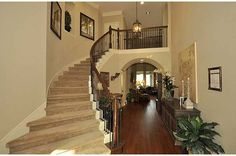 The curved staircase and arch beneath the balcony add elegance and an open feel. Coventry Homes, the White Oak Lake Estates community. Cypress, TX.