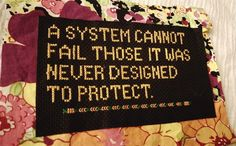A system cannot fail those it was never designed to protect. Unknown source - often attributed to W.E.B. Du Bois but seems to be some debate about whether it is. Cross stitched. Protest banner. Subversive cross stitch