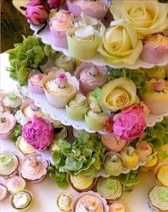 Cupcakes with swirly icing and hydrangea and roses.