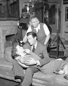 Director of photography Karl Freund gets a light reading of Katharine Hepburn and Robert Taylor on the set of Undercurrent