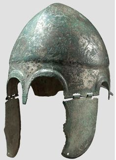 Chalcidian helmet, type V, early 4th century B.C. Late version of this helmet type with movable cheek pieces type V by Pflug. Skull with distinctive medial ridge, dividing the top into two hemispherical lobes. The edges of the cheek pieces are bent inward for 3 mm, the back extends almost vertically downward, and the front is characterised by two flat arches, at the lower end of the cheek-piece one perforation for a chin strap 29 cm high. Private collection, from Hermann Historica auction