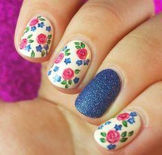 Uñas decoadas con rosas rosas y una uña color azul