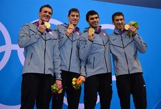 Ryan Lochte, Conor Dwyer, Ricky Berens and Michael Phelps (L-R) stand on the podium with their gold medals after the men's 4x200m relay victory