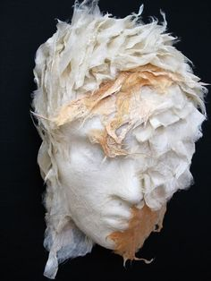 "Diane Hebert uses handmade paper as a medium for sculpture in her art exhibit, ""Masks"".  She uses Kozo bark pulp and fiber embedded with plant materials in her sculptures, ""leading the Kozo pulp and fiber in a dance with the plants and other natural materials"