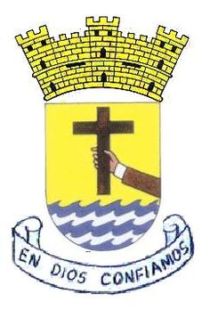 """Escudo de Penuelas, Puerto Rico. The adornment above the shield, a stone wall, represents the perpetuity. The cross represents Santo Cristo de la Salud that stopped the sea that flooded Peñuelas. The purple arm represents the priesthood and the town of Peñuelas. The canary yellow represents the sun. The blue and white symbolize the choppy sea and the regal ensign represents the faith in Christianity, """"In God We Trust""""."""