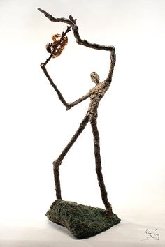 A tree man holds up a branch covered in larval cicada exoskeletons in the sculpture by Adam Long measuring approximately 20x10x12.