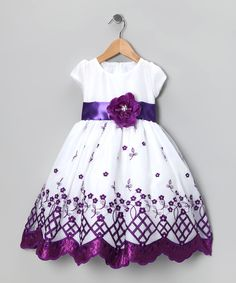 Add a touch of elegance to any occasion with this exquisite dress. A gorgeous flower at the waist, an embroidered floral-print skirt and a cap-sleeve bodice that zips up the back give this flawless frock some serious powers of enchantment. 100% polyesterMachine wash; tumble dryMade in the USA