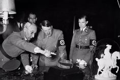 """Adolf Hitler admires and tiara and a sculpture of Napoleon at an unidentified location. Among Hitler's grand plans was the looting of art throughout Europe. He commissioned Albert Speer, his favorite architect, to prepare studies for a """"Fuhrer's Museum"""" to be built in Hitler's hometown, Lintz, Austria in order to house the best of """"Aryan"""" art. The museum was never built."""