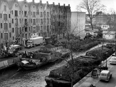 1959. Coal workers are unloading coal barges docked at the Achtergracht in Amsterdam. In the 1940's and 1950's the city of Amsterdam relied heavily on coal as a heating source.  After natural gas was discovered in the Noord of the Netherlands in July of 1959 the country transitioned quickly from coal to natural gas in the 60's. Photo Spaarnestad. #amsterdam #1959 #achtergracht
