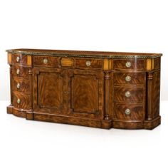 Donwell Buffet. A fine mahogany veneered and yew burl banded buffet, the break bowfront top with an ebony and brass inlaid edge, above an arrangement of four frieze drawers and central cabinet doors enclosing an adjustable shelf, flanked by two sets of three graduated drawers and turned and tapering columns, on line strung plinth base. #interiordesign #DiningRoom #theodorealexander