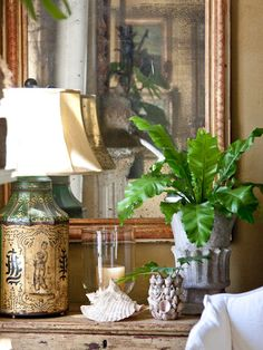 Dresser top display | Beige bamboo lamp, tall oak mirror, clear jar, art deco airplane, medium tapered pot with small birds nest fern.