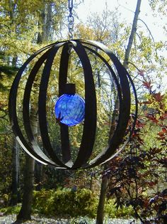 www.larksperennials.com GARDEN & YARD ART: I made this sphere from metal strappings that were on barrels. I put a hook in it so the sphere rota