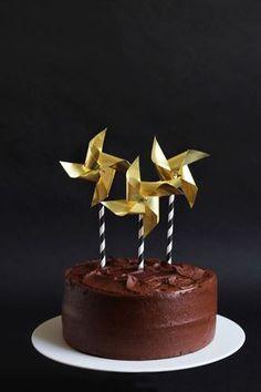 Topo de bolo de catavento dourado, preso em canudo listrado preto e branco em bolo de chocolate. Foto: Minted.com.