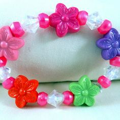 5 inch child's stretch bracelet with multi-color flower plastic beads, pink plastic spacer beads, and clear acrylic bi-cone beads http://ccsmallcreations.com/product/kids-flower-bracelet/  .****Please note that the bracelets should not be worn by children under the age of 3 without parental supervision as the small beads may be swallowed  if the bracelet were to break.****