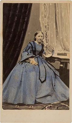 High bodice, open sleeves, pleated skirt with bow and sash, tinted blue. Black gimp trimming on bodice, sleeves and sash. Shown with collar and black trimmed undersleeves. PHOTO TREE
