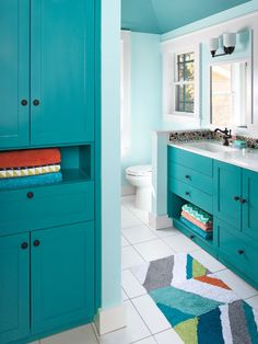 "In this bathroom, cabinets fronting the tub hide a hamper below a flip-down ""drawer"" for easy access. 