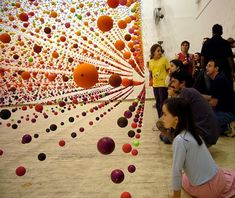 An immense array of suspended bouncy balls creating a dense field of color in the gallery space.
