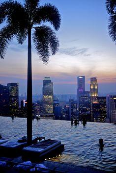 Die Dachterasse des Marina Bay Sands begeistert durch den Pool der sich über Singapur erhebt. Ein einmaliges Erlebnis die Abenddämmerung in Singapur von einem Hochhausdach zu genießen.