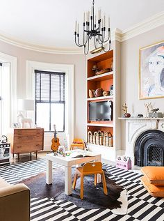 Nina Famrer's family play room is sophisticated and chic—love the layered cowhide rug over the striped area rug, and the wrought iron chandelier overhead.