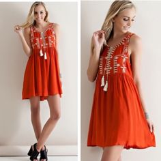Rust Boho Embroidered Tunic Dress A solid rayon tunic dress featuring contrasting embroidered detail on front bodice and tie-up tassel front closure. Color is Rust. Fully Lined. Non-Sheer. Woven. Lightweight. 100% Rayon. No trades. Dresses Midi