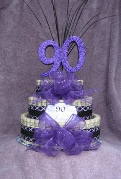 """Money Cakes from Creative Creations by MC, Is a great, unique and fun way to give a sweet treat you don't eat!  Send a Unique Fun Gift """"90th Birthday"""" say it with a money cake!  Money cakes are approximately 10"""" x 12"""" they are available in denominations of $25, $50, $75 $100, $150 and $200. The cakes are made with real money most cakes are made with $1, upon your request I can mix in $5's, $10's o"""