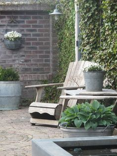 Love everything about this #garden - the hostas in the galvanised bins, the pond, the brick wall... #design #studiopaars
