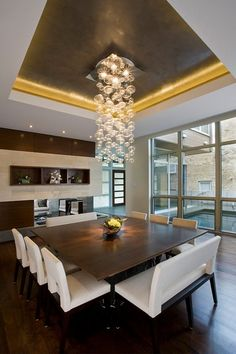 un lustre en cristal au-dessus de la table en bois carrée et les chaises blanches