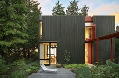 Not exactly metal, but the same effect could be achieved with vertically oriented corrugated metal panels, flanking a slice of color. Cedar clad home in Seattle.