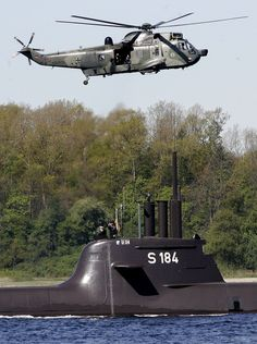 A German multi-purpose navy Westland Sea King MK 41 helicopter flies over a 212A-class U-34 submarine on the Baltic Sea off Eckernfoerde, northern Germany, on May 4, 2007. German defense officials have been left red-faced after a series of breakdowns delayed the first shipment of arms to Kurdish fighters in Iraq. AP