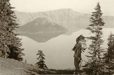 A Klamath chief in a ceremonial headdress looking out across Crater Lake, in the western end of the Klamath territory, Oregon, ca 1923. Photo by Edward Curtis.