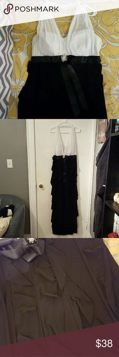 Floor length halter white and black dress A lovely floor length dress with a white, halter top. The bottom black has ruffles I tried to show in the third photo. Last photo shows some seriously tiny defects. Two pen point or smaller sized brown dots on the armpit area. And one small tear in the sheer material that goes around the neck. When you're wear the dress the material bunches up so you can't even see the tear. Betsy & Adam Dresses Prom