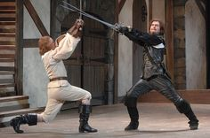 Stage combat: taught for the excitement within high degree of safety.  Notice the action/sword point is way above the head.... the man in black would be dead with such large movements. But the audience does not care or know ;)