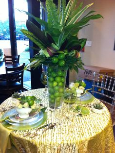 Glass tall vase filled with limes. Green arrangement with palm and aspidistra leaves. Floral design by Fillitwithflowers.com