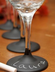 Great Idea!  Purchase some wine glasses (bulk) or dollor store, use chalkboard paint (either spray version or regular.)  The results are beautiful.  Having a low budget wedding does not mean it has to look like one.