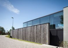 This house near the Belgian village of Knokke comprises a timber-clad ground floor with a glass box resting on top.