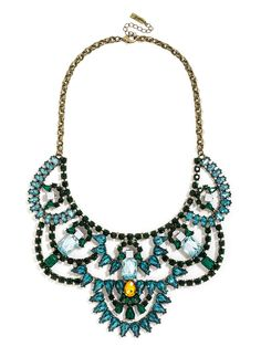 A colorful gem bib features intricate detail in a panelled statement necklace for a sweetly feminine touch with a slight dose of Renaissance flair.