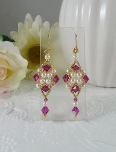 Woven dangle earrings with Fuchsia Swarovski crystals and creamy white crystal pearls.    These elegant hand woven earrings have Swarovski crystals in Fuchsia surrounding white crystal pearls and tons of tiny permanent finish golden seed beads showcasing a Swarovski crystal drop. Attached to hook style style ear wires the total length is 2.5 long and .75 wide.    Design by Sidonia Petki.    https://www.etsy.com/shop/IndulgedGirl