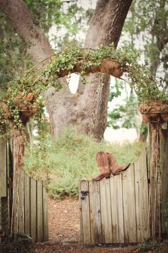 boots on wooden fence with ivy archway for entrance into a rustic chic style wedding | Photo: Papered Heart Photography